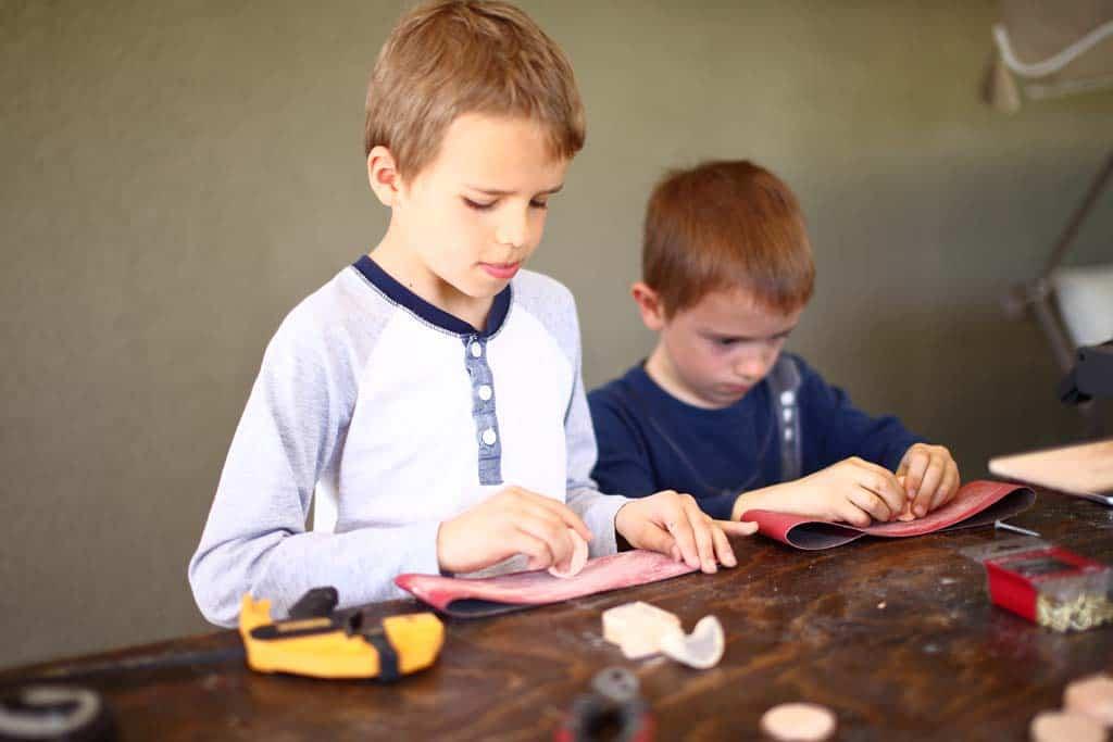 boys are sanding the discs for DIY Family Calendar Board