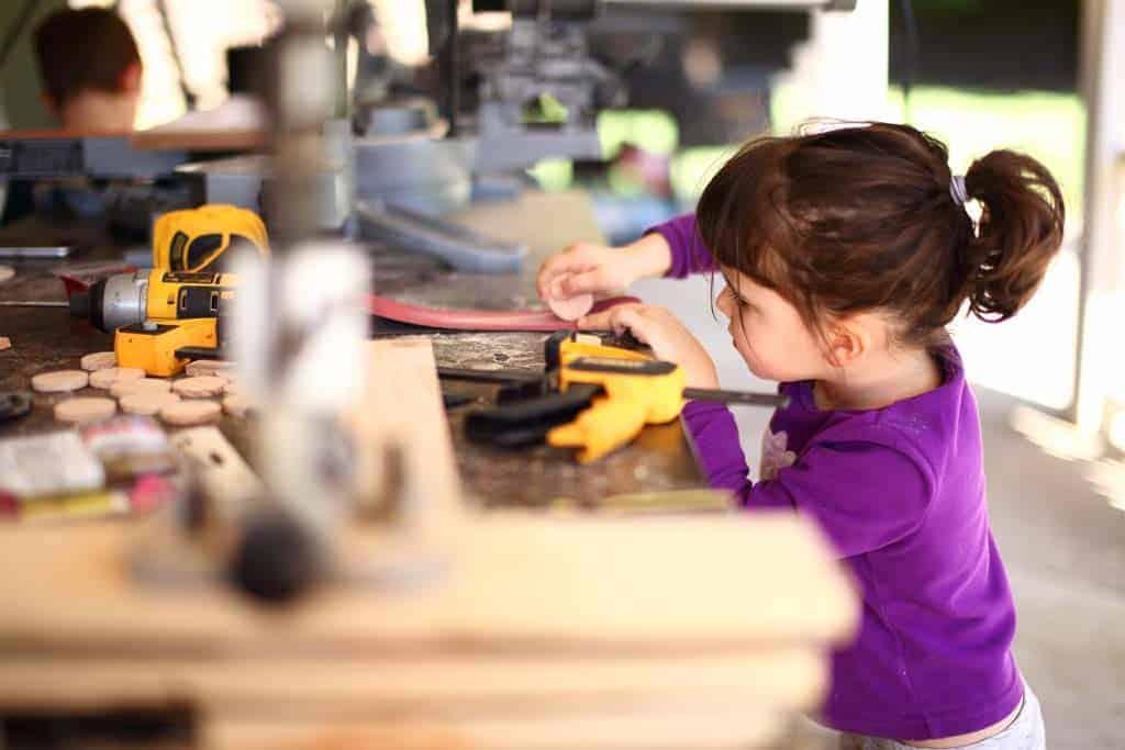 girl sanding wood discs for DIY Family Calendar Board
