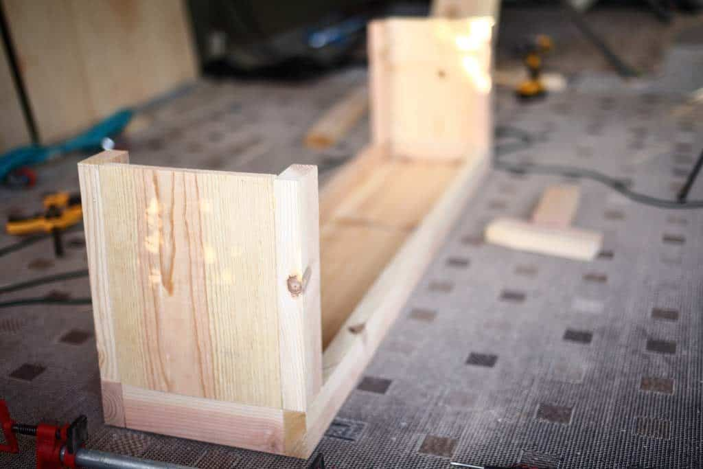 attaching legs to the bench with storage