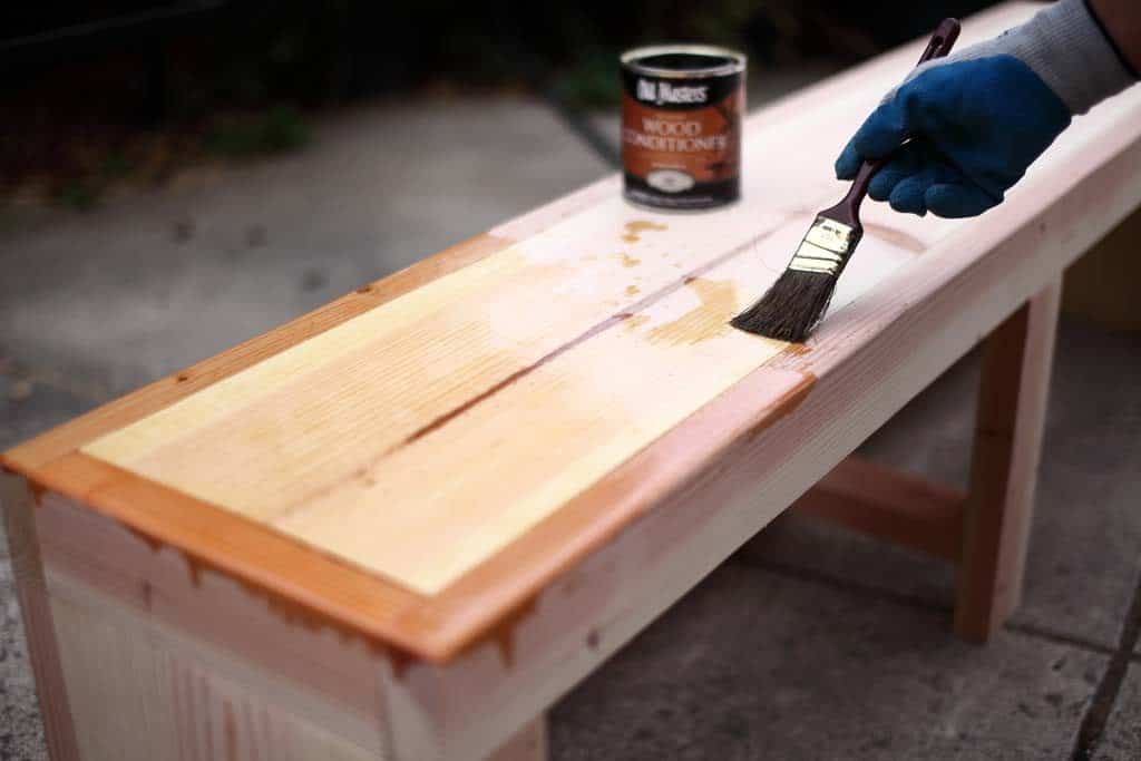 applying pre-stain for DIY Bench with Storage