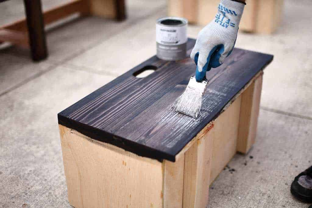 brushing white paint over stain for DIY Bench with Storage