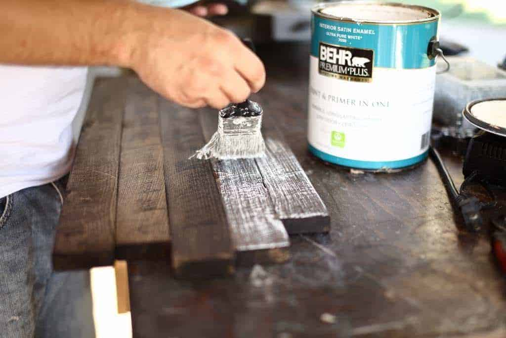 brushing white paint over diy rustic kitchen sign