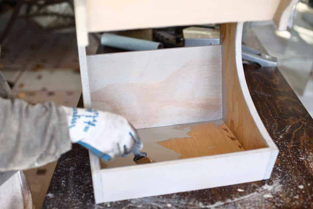applying pre stain on DIY Fruit Storage Container
