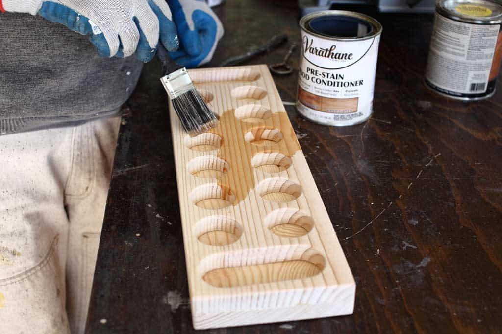 applying pre stain on DIY Mancala Board Game