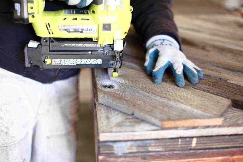 using nail gun for the DIY Reclaimed Wood Frame Sign