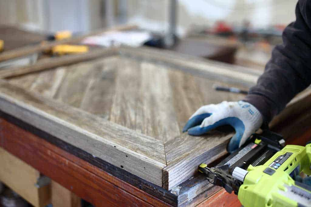 using nail gun for DIY Reclaimed Wood Frame Sign
