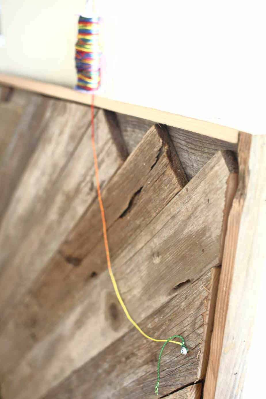 attaching string to hang the DIY Reclaimed Wood Frame Sign