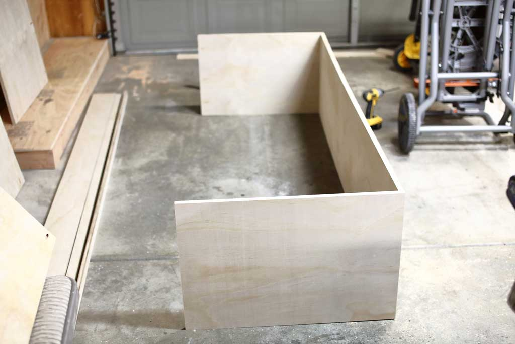 attaching side and bottom piece together for the DIY Garage Cabinets