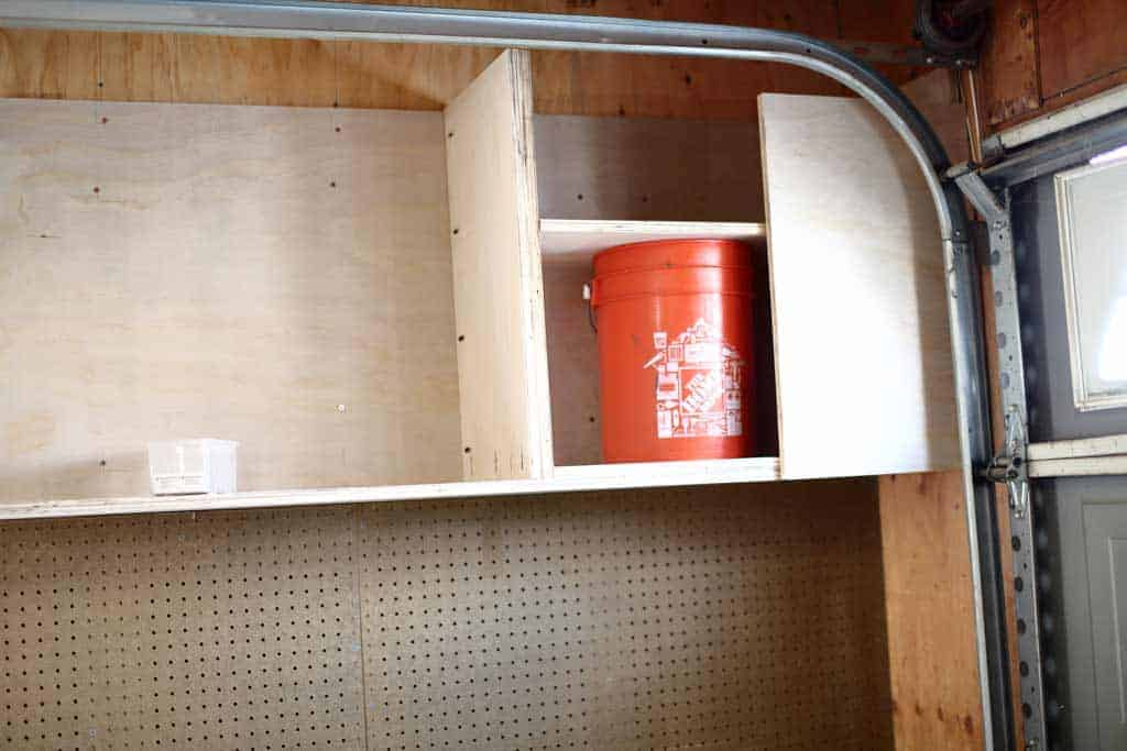 using a bucket as a guide to attach dividers of the garage cabinets