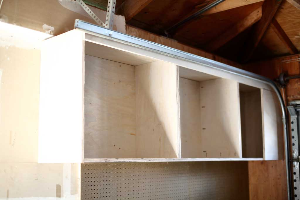 attaching the top piece of the garage cabinets