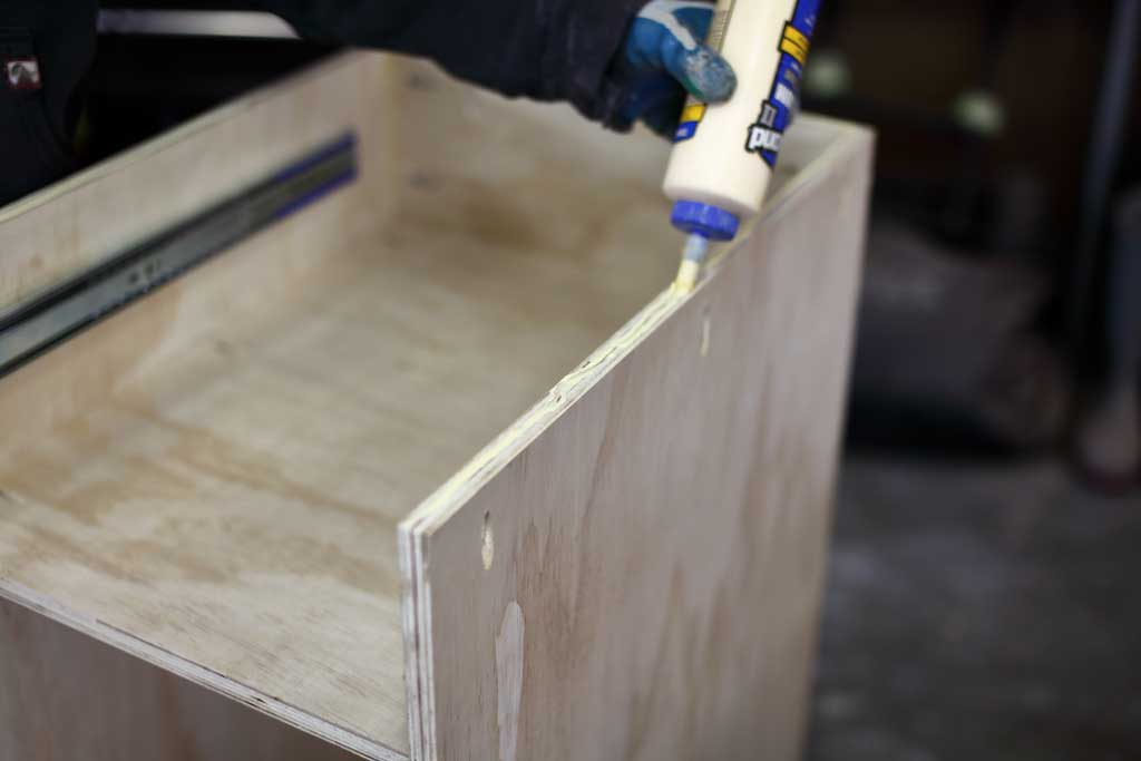applying wood glue on plywood