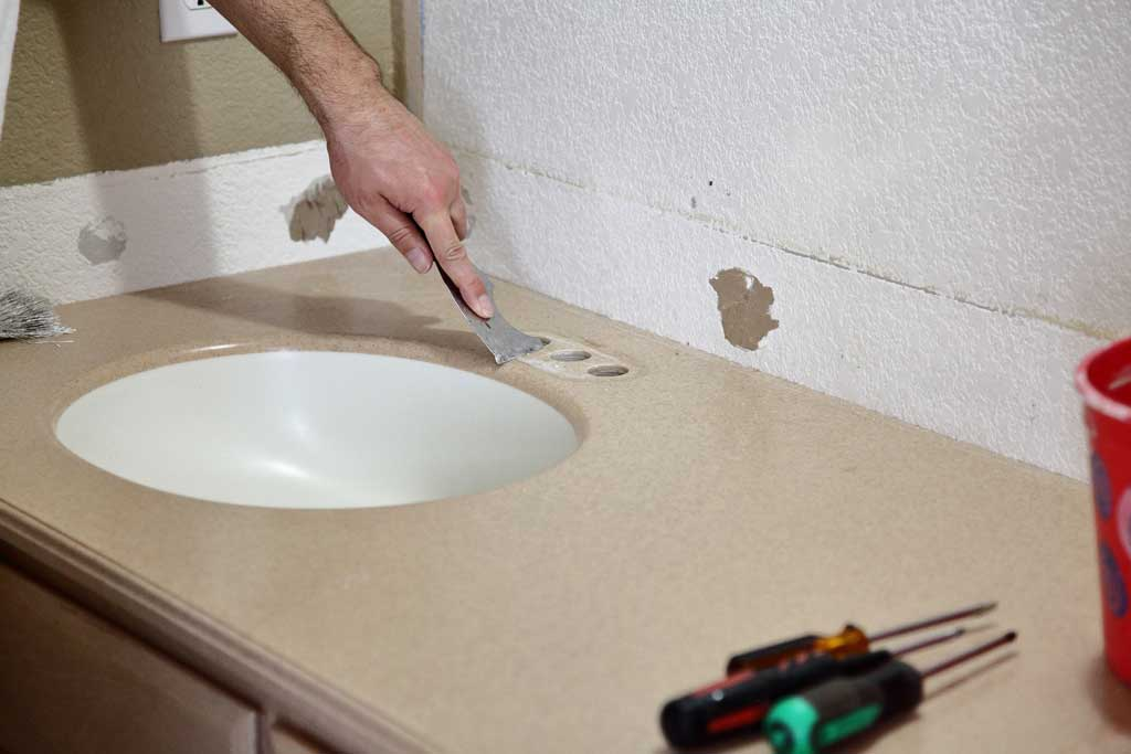 scraping buildup from counter top around fausets