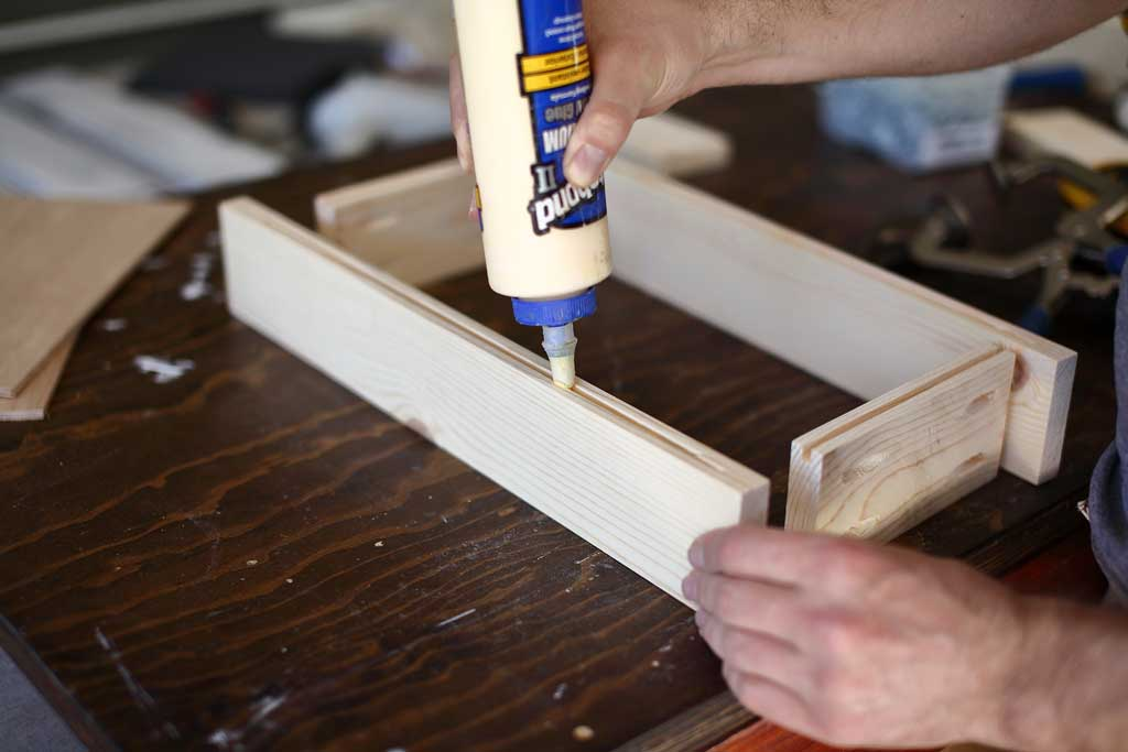 applying wood glue in groove for plywood panel