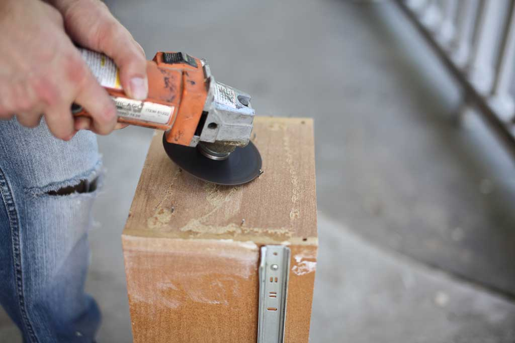 using grinder to cut off staples from drawer