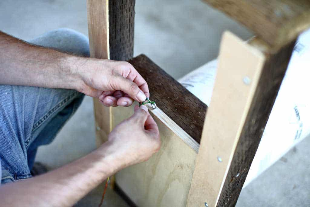 tying the string to the front door of the DIY skunk trap