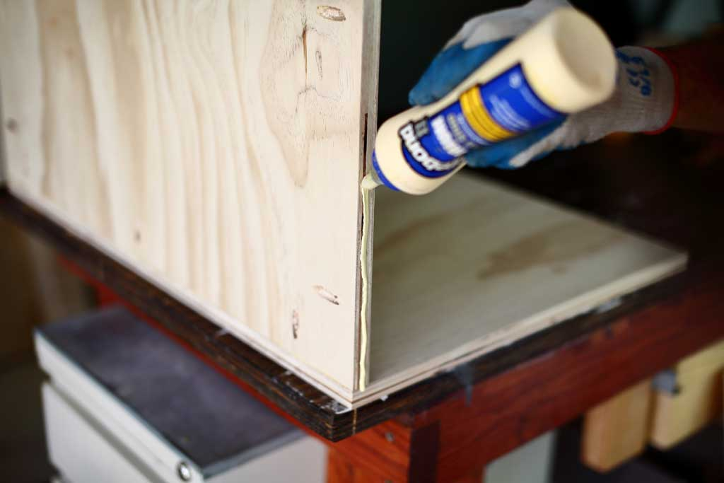 applying wood glue to the side of the cabinet