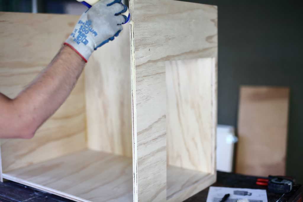 applying wood glue to the front of the cabinet
