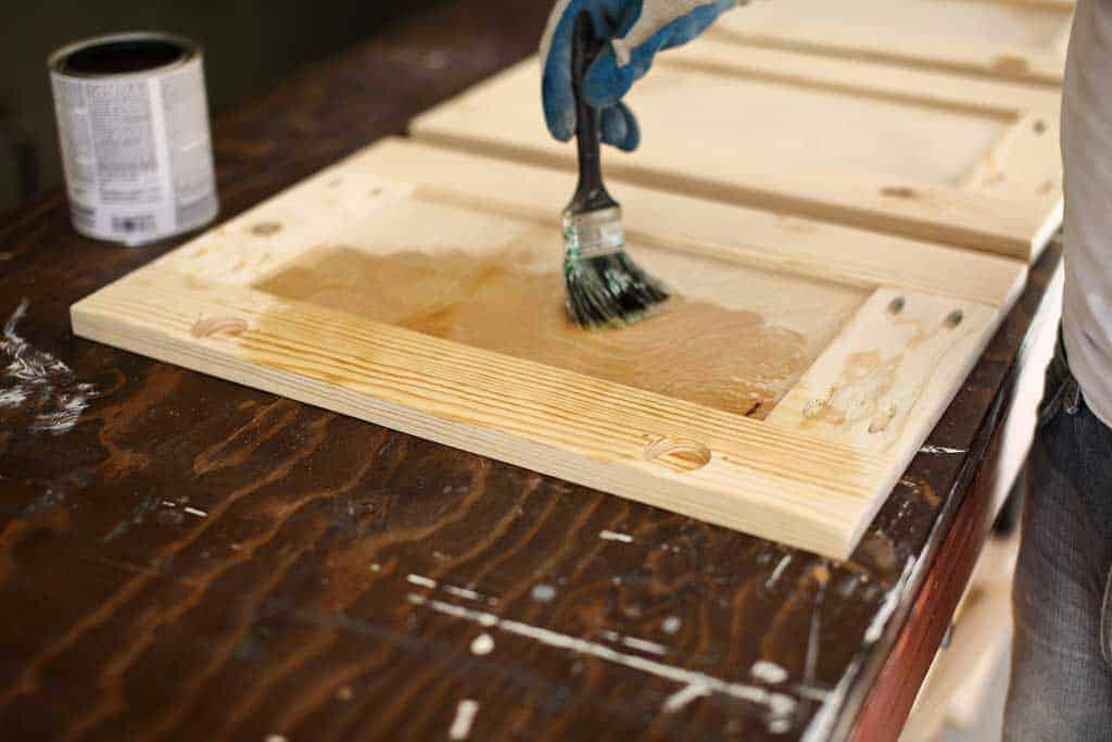 applying pre-stain to the cabinet door