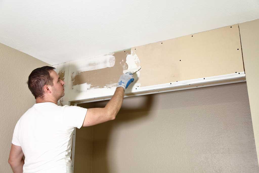 applying drywall mud over sheetrock