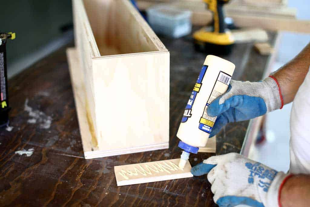 gluing plywood trim around diy flower planter box
