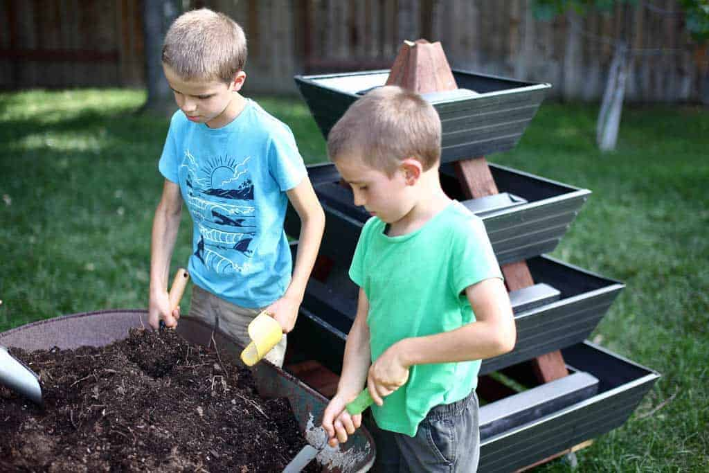 kids filling gutters with soil