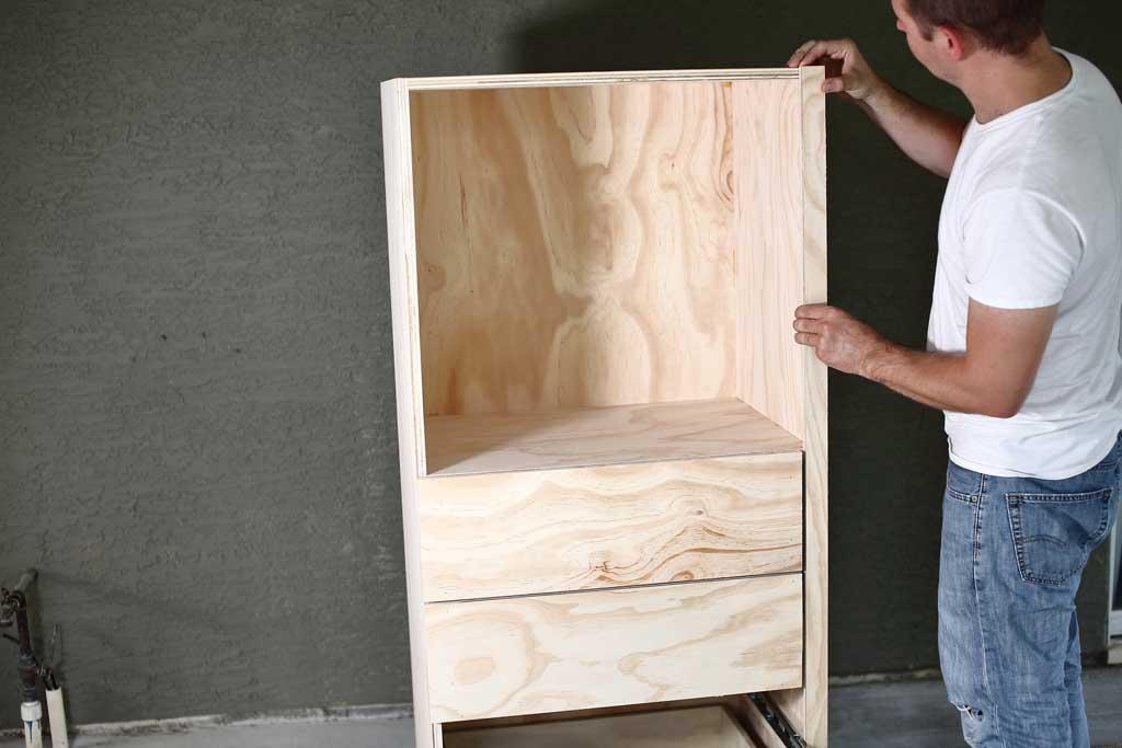 attaching plywood board to the DIY closet organizer