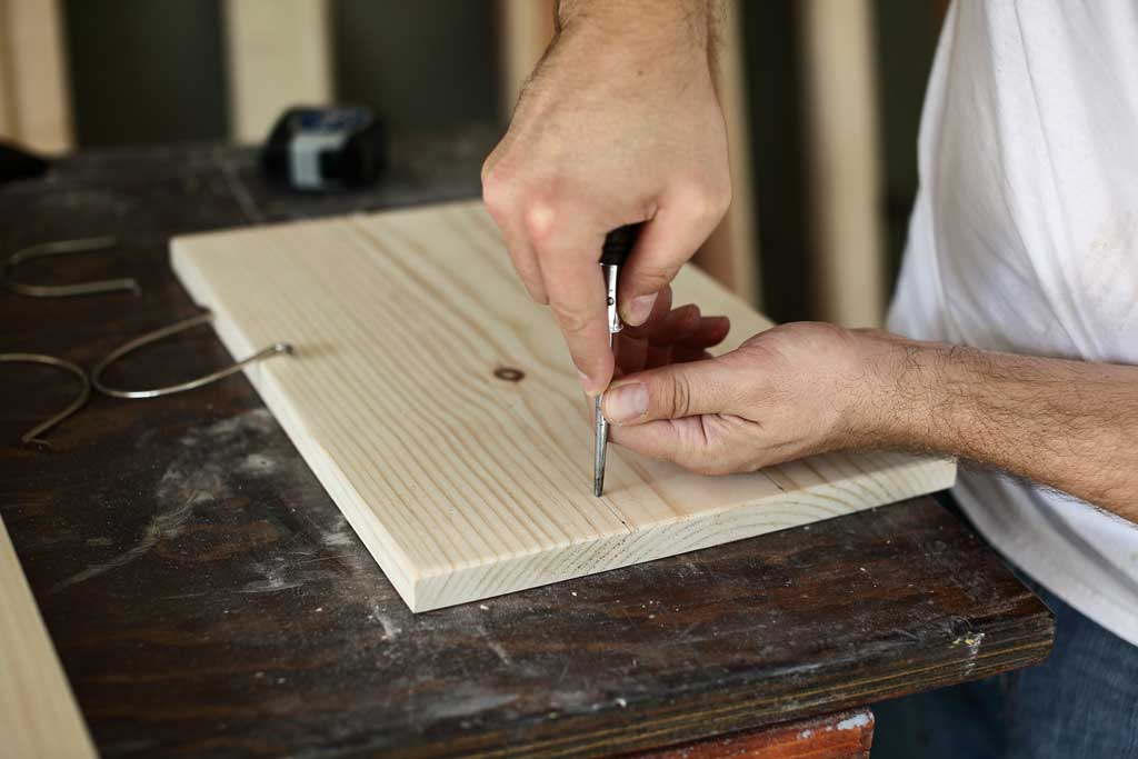 using a scratch awl to mark the board