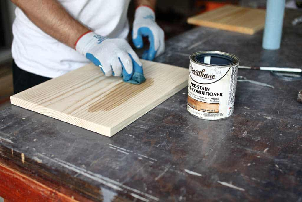 applying pre-stain on the pine board