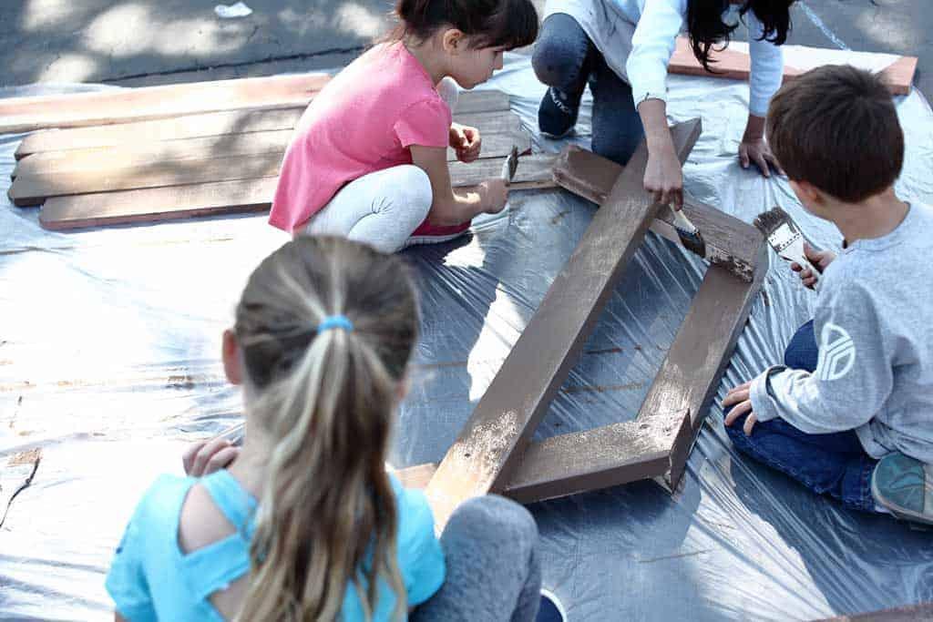 kids painting legs for the sandbox