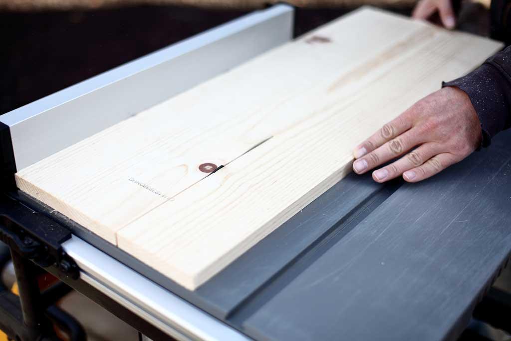 cutting wood on table saw for DIY bird feeder house
