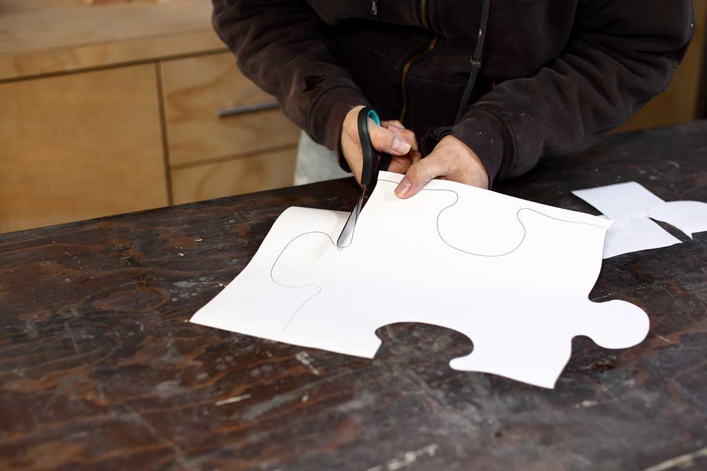 cutting out puzzle template with scissors