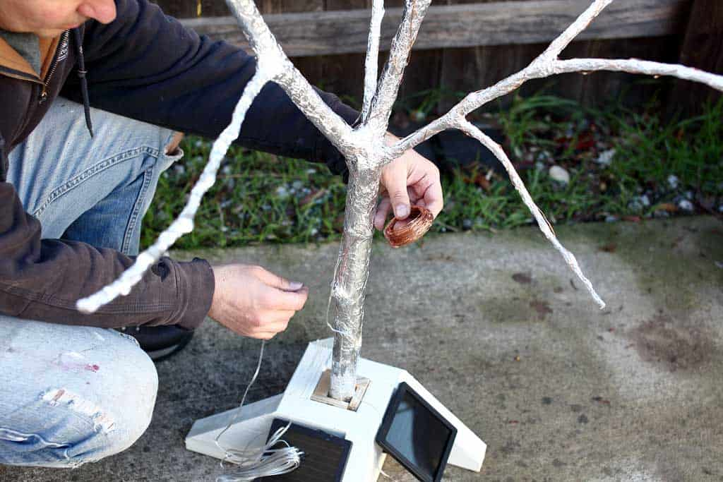 wrapping copper wire with lights around the fairy tree
