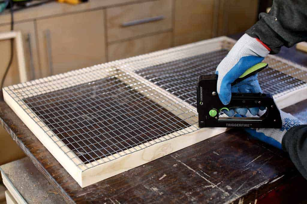 stapling wire mesh screen to floor frame of DIY rabbit hutch