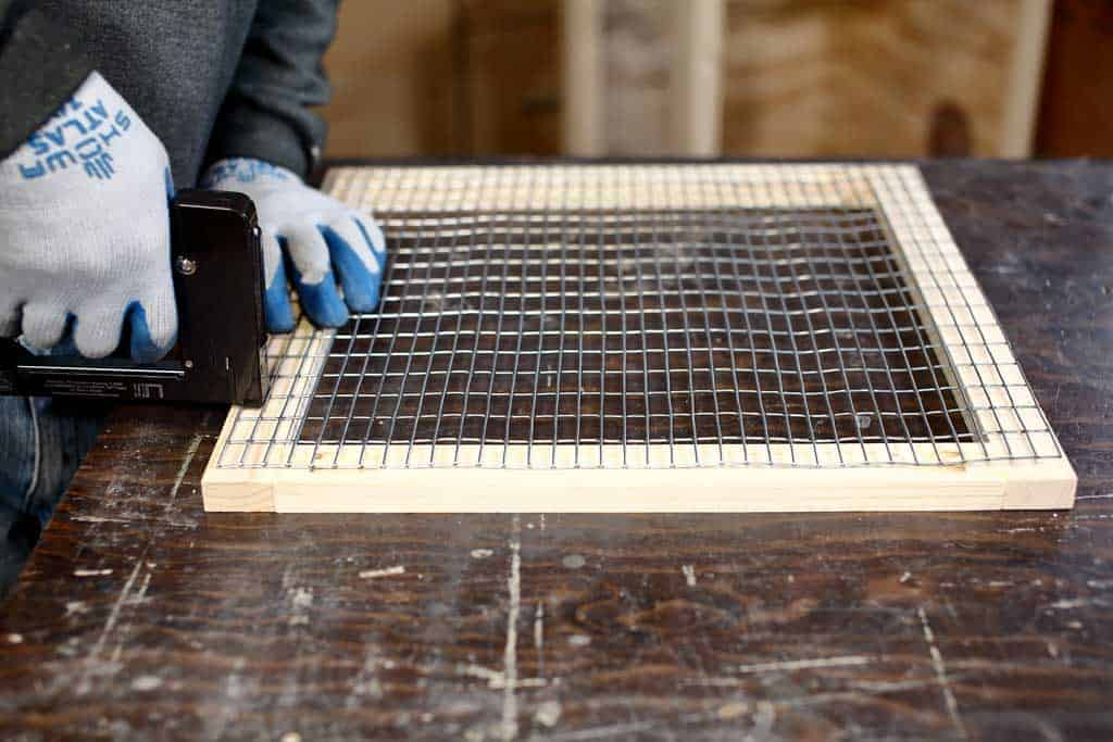 attaching wire mesh screen to the door of the DIY rabbit hutch