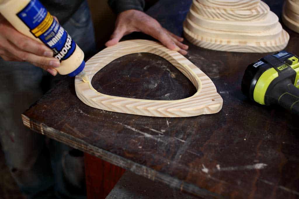 applying wood glue to birdhouse