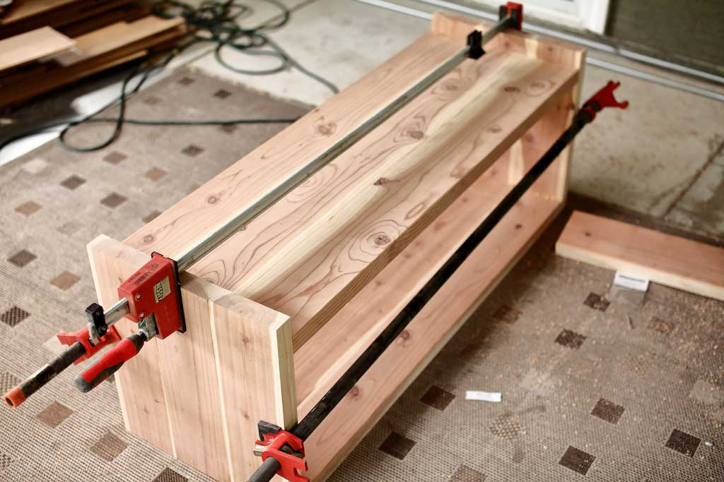 clamping the bench together for glue to dry